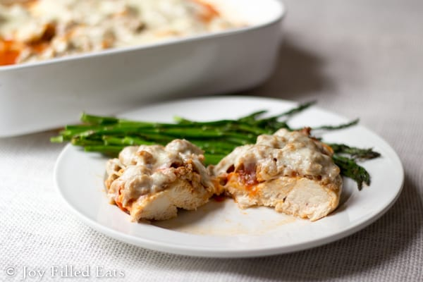 Italian Sausage Baked Chicken on a white plate with asparagus