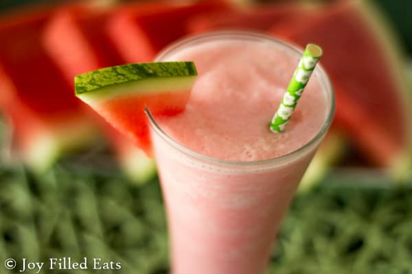 close up overhead view on a watermelon smoothie in a tall glass garnished with a fresh watermelon slice and paper straw placed on the glass rim set next to a platter of watermelon slices