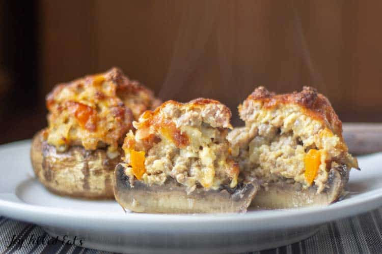 Sausage Stuffed Mushrooms cut in half on a white plate with steam rising
