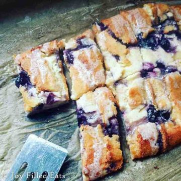 braided blueberry cheese danish bars lined on a table with a serving spatula
