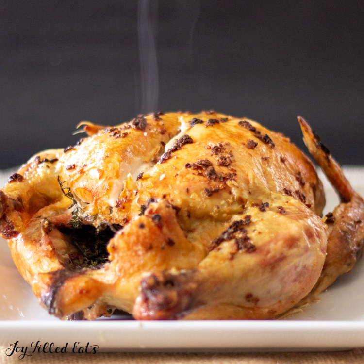 garlic roast chicken on a platter with steam rising
