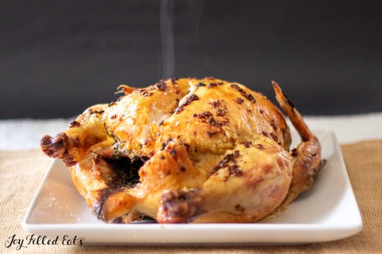 Garlic Herb Butter Roast Chicken on a platter with steam rising