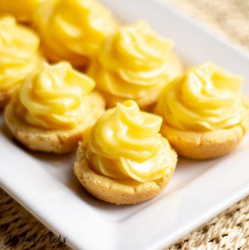 mini lime tartlets lined on a white rectangular platter