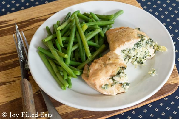 two halves of a spinach & artichoke stuffed chicken breast on white plate served with a side of green beans set on a cutting board next to a fork and knife