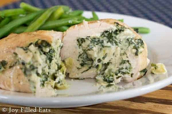 A Spinach Stuffed Chicken Breast cut open on a white plate to show the filling