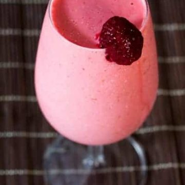 close up on a frozen raspberry cocktail mocktail with a strawberry garnish on the rim