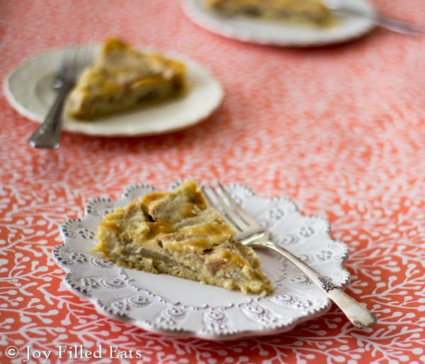 slices of low carb pear custard pie on white plates with forks arranged on a decorative table cloth