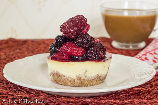 A mini keto cheesecake on an ivory plate topped with a pile of berries.
