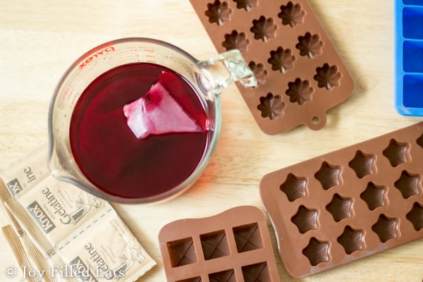 measuring cup of brewed passion tea surrounded by candy molds from above