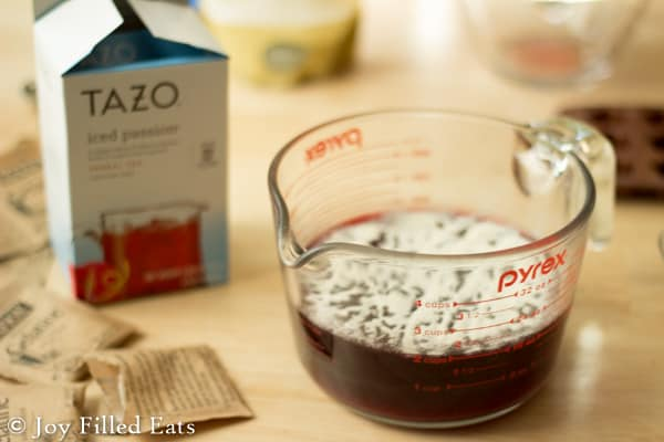 measuring cup half full of brewed passion tea next to a box package of tazo tea