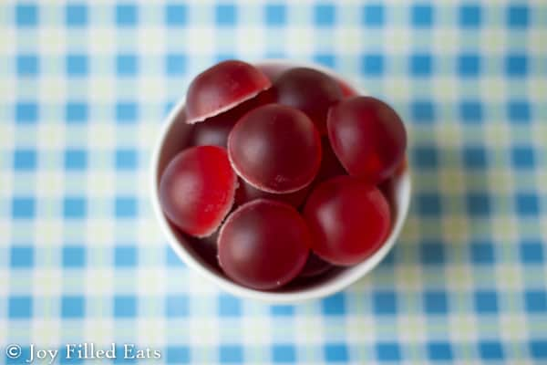 overhead view of gumdrop shaped homemade red gummies in a small white dish