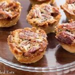 close up on mini pecan pies on a small, round glass plate