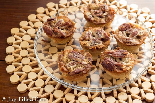plate of mini pecan pies on a small glass plate set on a cork place mat