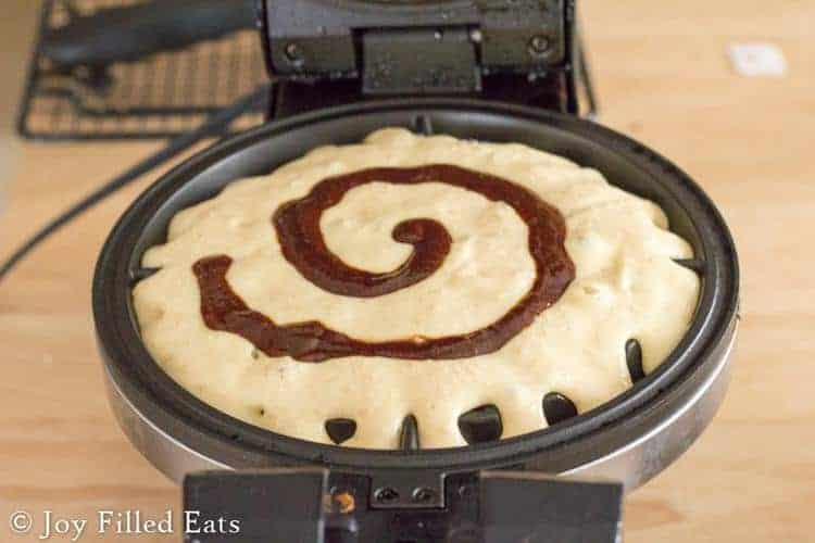 cinnamon roll waffle batter with a cinnamon swirl poured into an open waffle iron