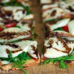 close up on slices of fresh mozzarella & arugula grilled pizza
