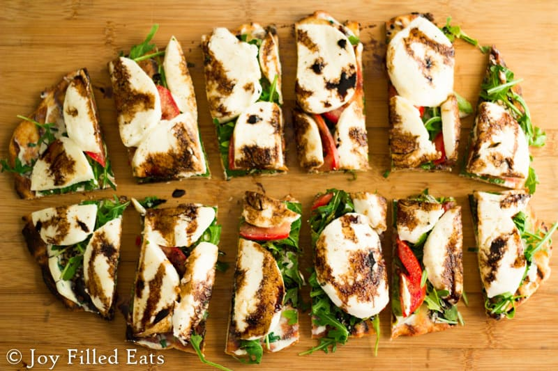 Fresh Mozzarella & Arugula Grilled Pizza cut into pieces on a cutting board