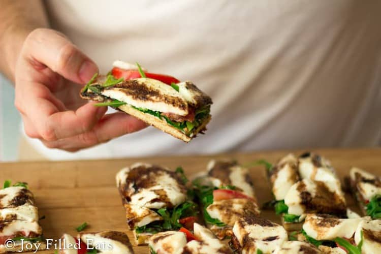 hand lifting slice of fresh mozzarella & arugula grilled pizza from table with more slices