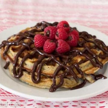 white plate full of chocolate covered raspberry waffles topped with chocolate ganache filled raspberries