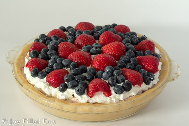 low carb berries and cream ice cream pie topped with strawberries and blueberries in a glass pie plate