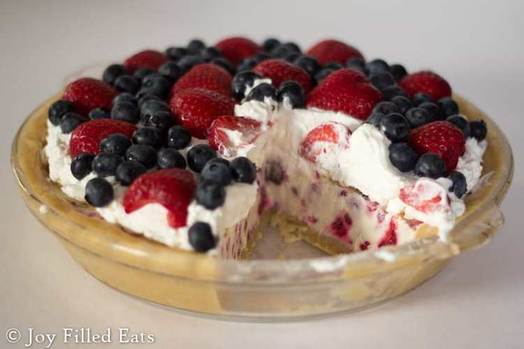 a no bake ice cream pie in a glass pie plate with one slice missing