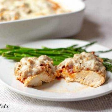 Italian baked chicken with sausage serving cut in half on a plate with green beans set in front of casserole dish