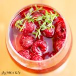 overhead view of a glass of keto sangria filled with raspberries and topped with fresh thyme