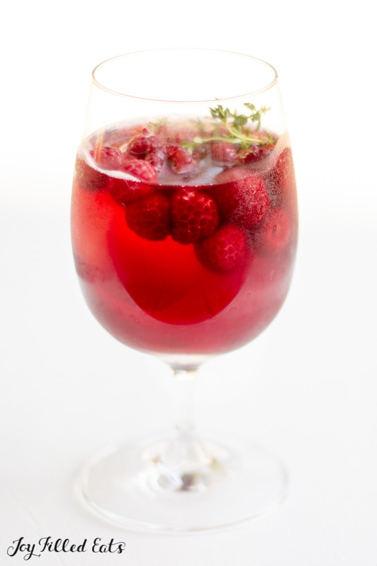 a glass of keto sangria with raspberries and thyme