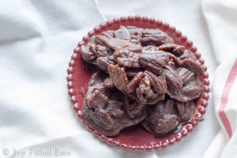 pile of chocolate pecan pralines on a red plate from above