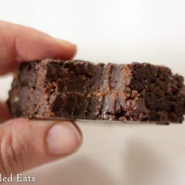 hand holding a keto fudge brownie with large bite missing