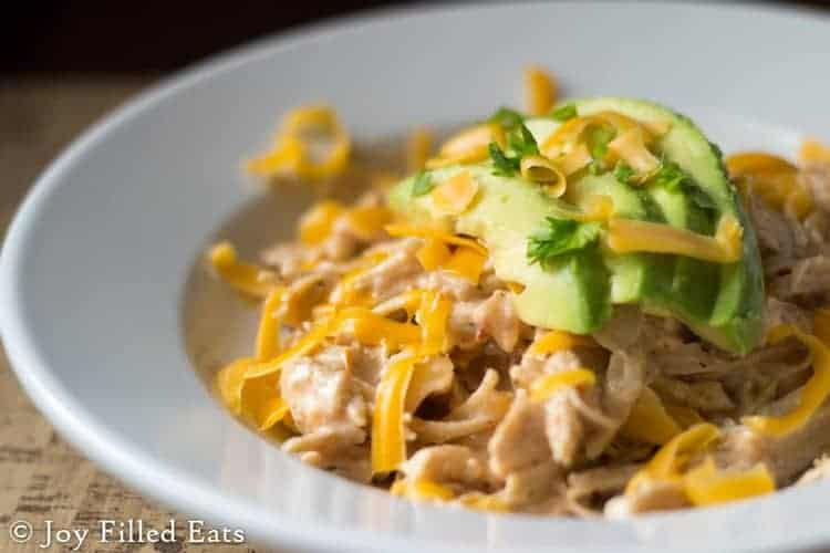 close up of shallow bowl full of Instant Pot Mexican Chicken topped with shredded cheese and sliced avocado
