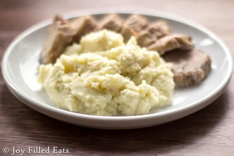 Big scoop of the best mashed cauliflower you will ever try next to sliced pork