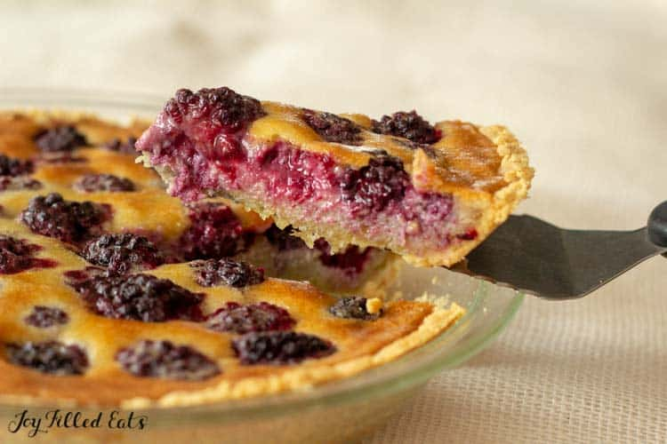 a pie server lifting up a slice of the blackberry custard pie