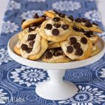 pile of two bite chocolate chip cheese danishes on a white cake plate set on a decorative blue table cloth