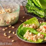three Thai chicken salad lettuce wraps on a plate next to a container of chicken salad and platter of lettuce leaves