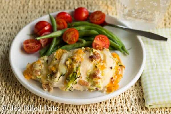 Four Cheese Bacon Hasselback Chicken on a wide plate with green beans and tomatoes