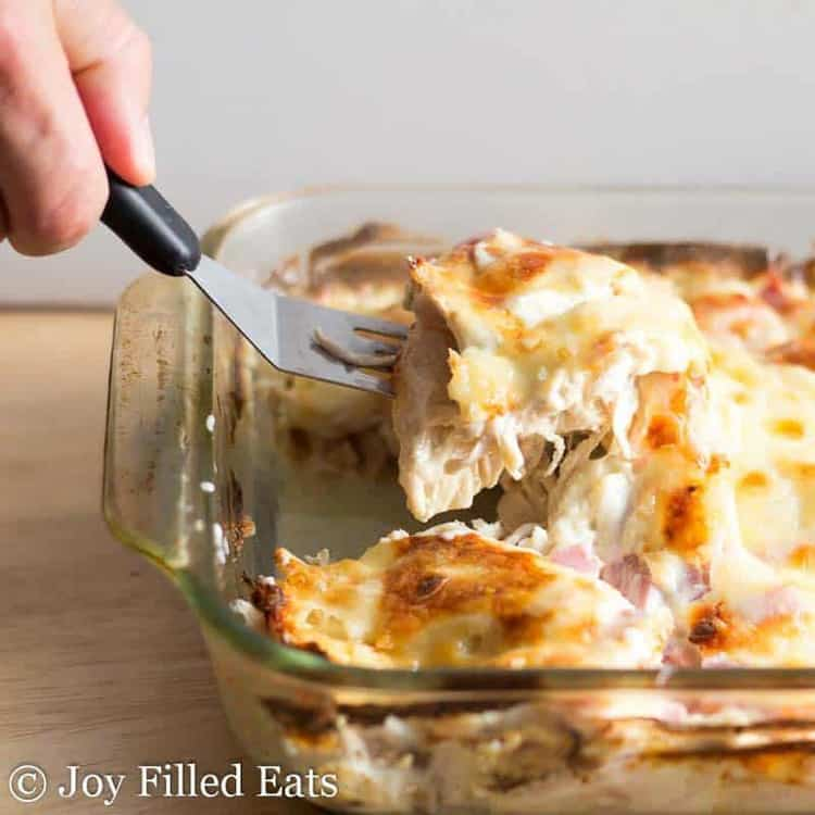 A hand holding a spatula lifting a piece of chicken casserole with gooey cheese