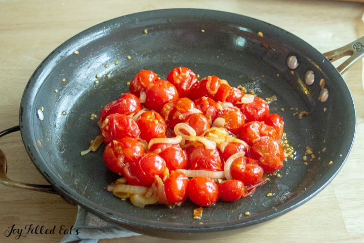 cherry tomatoes, onions and garlic cooking in skiller
