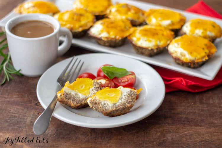 Sausage Egg Muffin cut in half on plate with fork and halved cherry tomatoes. Cup of coffee and sheet pan of Sausage Eff Muffins next to white plate