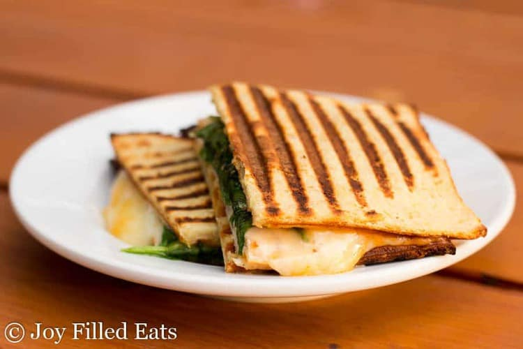 two halves of a turkey cheddar chipotle panini on a white plate
