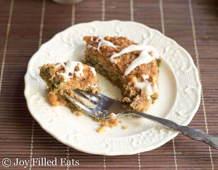 bite of pumpkin dump cake on a fork resting on a white plate with a slice of pumpkin dump cake