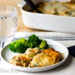 Tuscan chicken casserole portion served with broccoli florets on a white plate next to a fork and napkin, bubbling water in a glass and white casserole dish