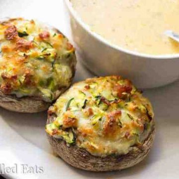 two cheese stuffed mushrooms with bacon on a white plate next to a bowl full of soup