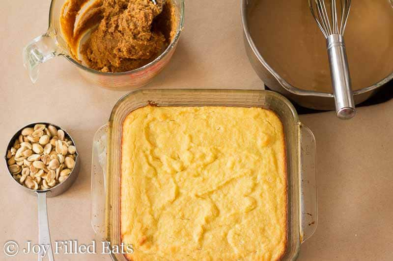 yellow cake in a square baking dish surround by ingredients for caramel peanut butter payday cake
