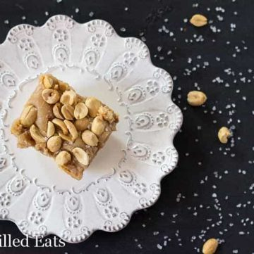 overhead view of peanut butter cake with caramel icing and topped with peanuts on a white plate