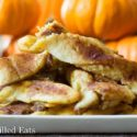 pile of keto pumpkin pie twists on a white plate set in front of a pyramid of mini pumpkins