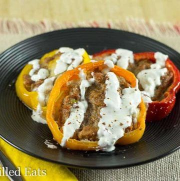 taco stuffed pepper rings drizzled with sour cream on a black plate next to a yellow napkin and fork