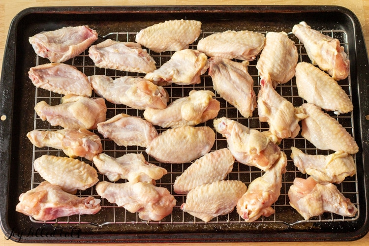 raw chicken wings lined on a cooling rack placed in a sheet pan