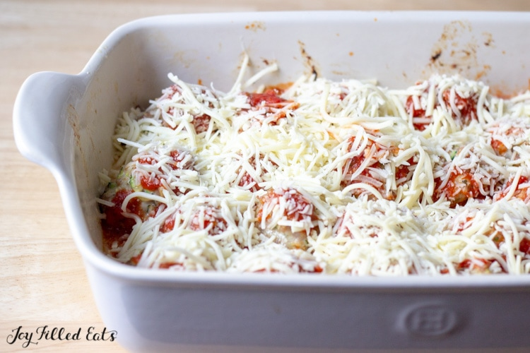shredded cheese covering meatballs and sauce layered in a white casserole dish