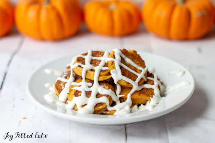 plate of pancakes with drizzled in cream cheese icing set in front of a row of pumpkins