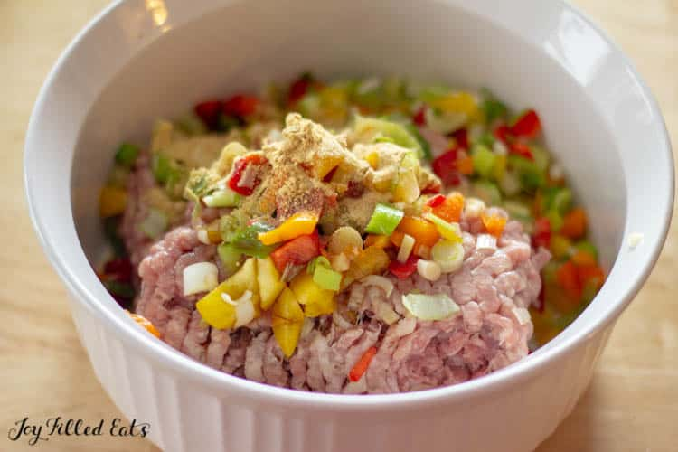 ground meat, chopped veggies, and seasonings in a white bowl
